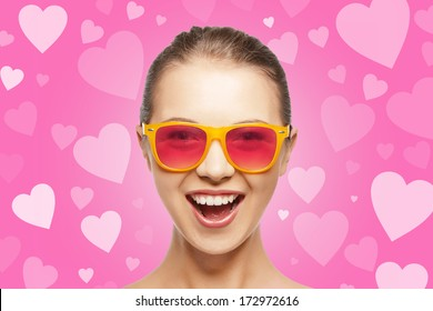 love, happiness and valentines day concept - amazed teen girl in pink sunglasses on background with hearts