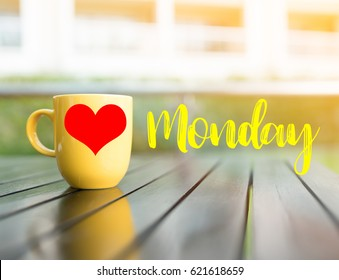 Love and Happy Monday word.yellow cup of coffee and red heart shape on yellow cups on table.