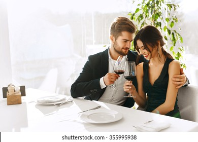 Love. Happy Romantic Smiling Couple Having Dinner, Embracing, Drinking Wine, Celebrating Holiday, Anniversary Or Valentine's Day In Gourmet Restaurant. Romance, Relationships Concept. Celebration