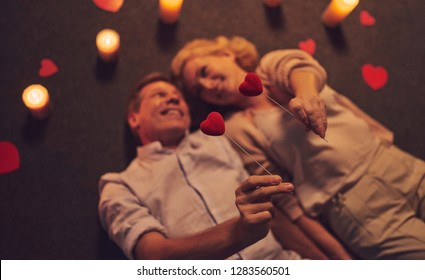 Love has no age! Romantic senior couple celebrating Saint Valentine's Day at home. Beautiful woman and handsome man enjoying spending time together. Happy Saint Valentine's Day!