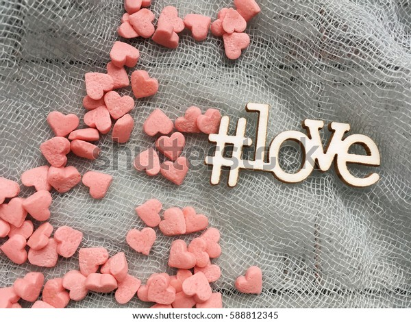 love hashtag for instagram. Hashtag wooden love. Love on grey textile.