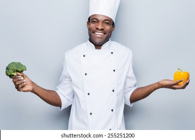 In love with healthy food. Cheerful young African chef in white uniform holding pepper in one hand and broccoli in another while standing against grey background