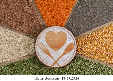 Love healthy food concept with colorful grains and seeds surrounding wooden board displaying heart and cutlery shapes drawing in flour