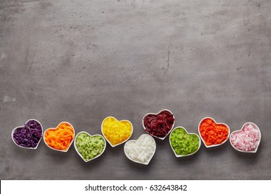 Love for healthy food concept with little heart-shaped white bowls of grated vegetables of different colors in a row on grey surface background with copy space