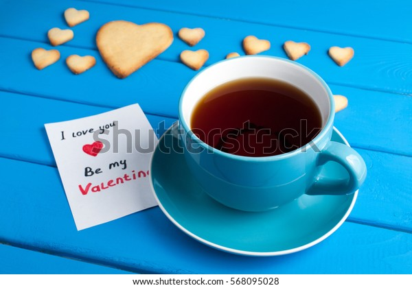 Love heart with cups of tea on a blue wooden table. Valentine's Day.