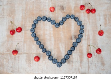 love heart made of big blueberries and widespread red cherries on vintage wooden background.