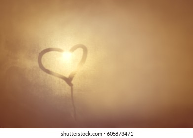 A love heart painted on a misted glass window background. Close up photo of lovely emotional mood draw