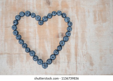love heart shape formed by big blueberries, vintage wooden background, copy space on the wooden board
