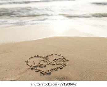 Love and heart symbol on sand with sea beach for happy Valentine's day greeting celebration and summertime welcome.