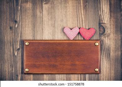 Love hearts, signboard frame on vintage wood background