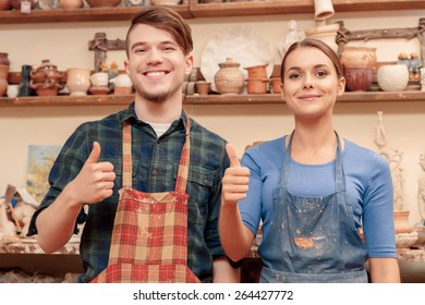 In love with the hobby. Two cheerful young people showing their thumbs up standing in a clay studio