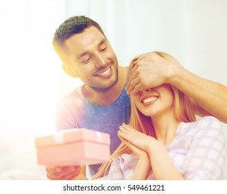 love, holiday, celebration and family concept - smiling man surprises his girlfriend with present at home