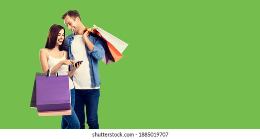 Love, holiday sales, shop, retail, consumer concept - happy smiling couple with shopping bags, and cellphone. Green background.