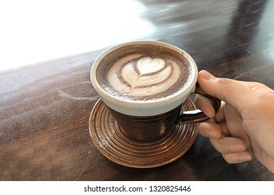 love hot latte heart coffee hearth shape on a cup of coffee on wood table from top view and caching coffee cup with hand