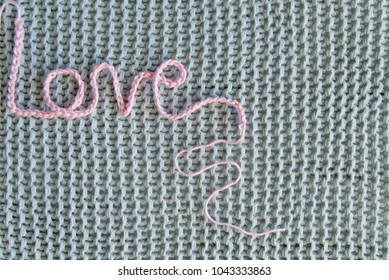 love inscription in pink threads lies on a blue knitted background