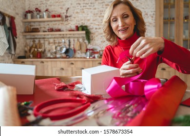 Love it. Cheerful aged woman sitting at the table and cutting pink ribbon for decor