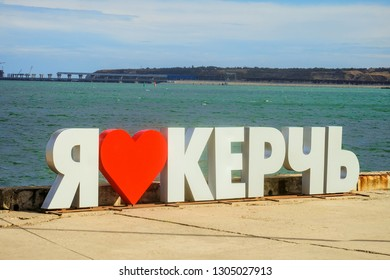 I Love Kerch. Big white letters with simple symbolic red heart at Crimean Kerch promenade. Crimean bridge in the background.