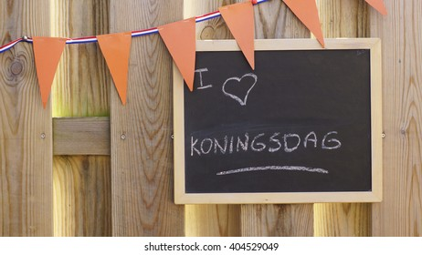 I love Kingsday in Dutch written on a chalkboard hanging in the sun with a orange flag