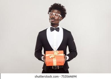 Love, kiss,celebration concept. Romantic man send kiss at camera and holding gifts. Studio shot