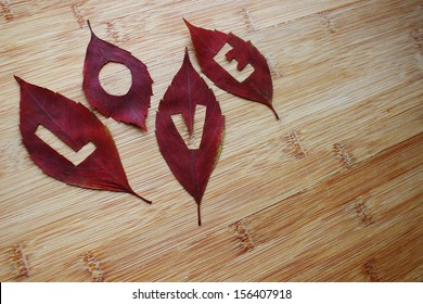 Love in leaves on a wooden background