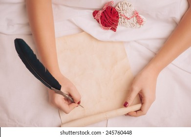 Love letter. Closeup image of woman writing a vintage letter with copy space to valentines day with feather pen while lying in bed