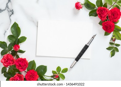 Love letter concept. Blank paper card, fountain pen, roses flowers on white marble desk. Minimal flat lay style composition, top view, overhead.