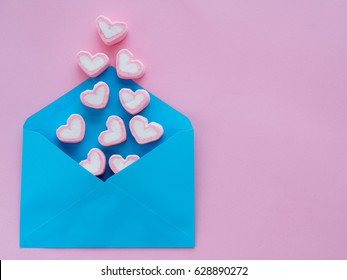 Love letter valentine's day concept. Closeup image of blue letter with copy space arranged on pink background  and colorful of hearts