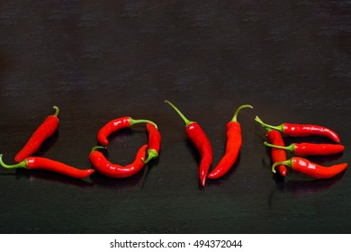 Love lettering made of chili peppers on wooden black background