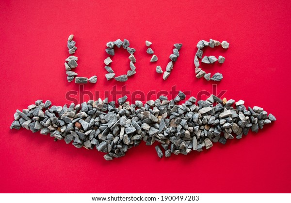 "The ""LOVE"" letters from many small stones or pebbles are the concept of Valentine's Day or Love Day and are placed on a red background. Taking top view and close-up"