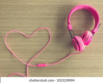love and listen to your heart concept, The image of sweet pink headphones The line was wrapped into a heart shape to convey the love. background is beautiful wooden table.