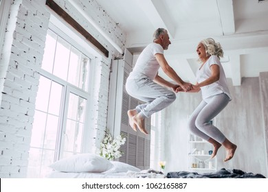 Photo of Love lives forever! Senior couple at home. Handsome old man and attractive old woman are enjoying spending time together. Having fun and jumping in bed.