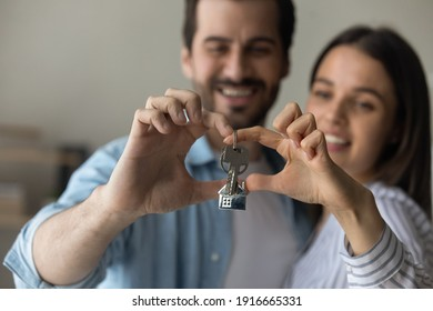 Love lives here. Happy caring millennial family couple posing at new home house cuddling making heart shape of fingers with bunch of keys inside. Focus on joined hands of spouses holding key. Close up