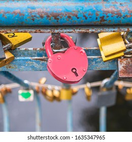 Love lock that sweethearts lock to a bridge to symbolize their love. Close up of pink heart shaped padlock