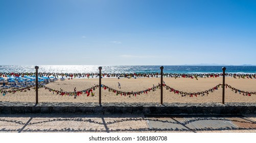 love locks, beach and ocean in Puerto del Carmen boardwalk, Spain. Puerto del Carmen is the main tourist town on the island of Lanzarote