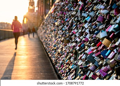 Love Locks in evening light at a fence on the Hohenzollernbridge in Cologne. A Jogger is passing by. Couples places these locks at the fence as a symbol of their love.