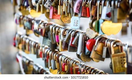 Love locks on the butchers bridge in Ljubljana Slovenia. Bridge full of colorful love padlocks hanging from fence with names written on it. Mesarski most, Ljubljana, Slovenia.