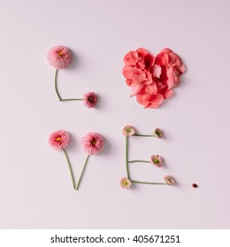 """""""Love"""" made of flowers and petals on white background. Love concept. Flat lay."""