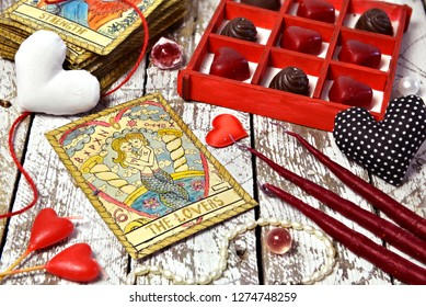 "Love magic ritual with red candles, tarot card Lovers, heart symbols and chocolate candies.  The English title on the card ""Lovers"" means the word ""lovers"".  Romantic vintage valentine's day concept"