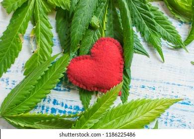 Love and marijuana. Red heart against the background of marijuana leaves.