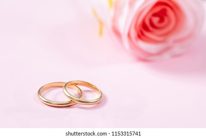 5a3ad7e35 Love and marriage concept. Close up view of golden wedding rings and a  blurry pink