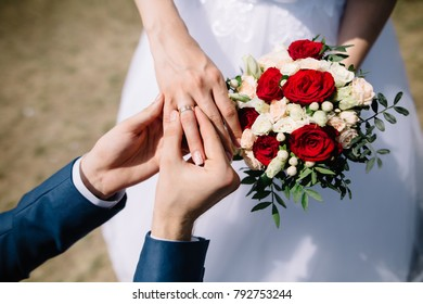 Love and marriage. Fine art rustic wedding ceremony outside. Groom putting golden ring on the bride's finger. Bouquet of red and white roses in hands. Closeup view