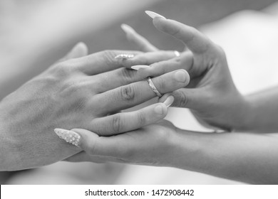 Love and marriage. Wedding ceremony. Close up of bridge putting golden ring on the groom's finger