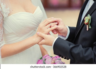 Love and marriage. Wedding ceremony. Close up of groom putting golden ring on the bride's finger.