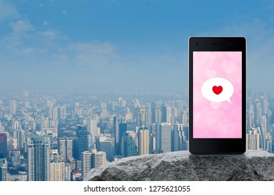Love message chat icon on modern smart mobile phone screen on rock mountain over modern city tower, office building and skyscraper, Business dating online connection, Valentines day concept