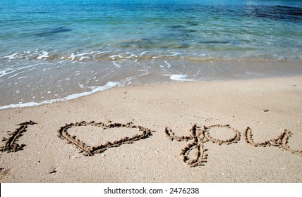 Love message on gold sand and sea waves