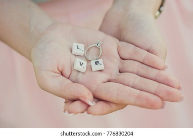 love message with scrabble pieces and engagement ring