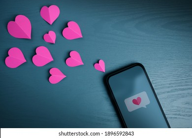 Love Message. Valentines Day Concept. Sending Heart Symbol to someone via Mobile Phone. Top View