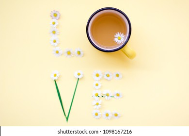Love message written with flowers on yellow background. Individual Love concept.