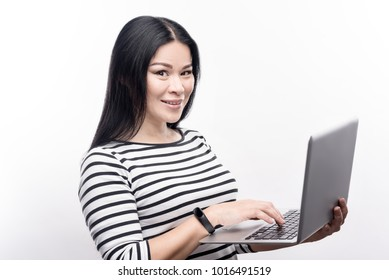 Love modern technologies. Beautiful dark-haired young woman in a striped pullover working on her laptop and posing for the camera while standing isolated on a white background