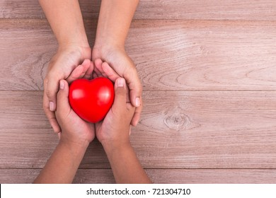 Love Mom Concept : Woman holds her young kids hands supporting red heart on brown wooden table background. Free space for text of Mother's Day celebration.